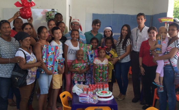 Students and adults pose in front of snacks and gifts